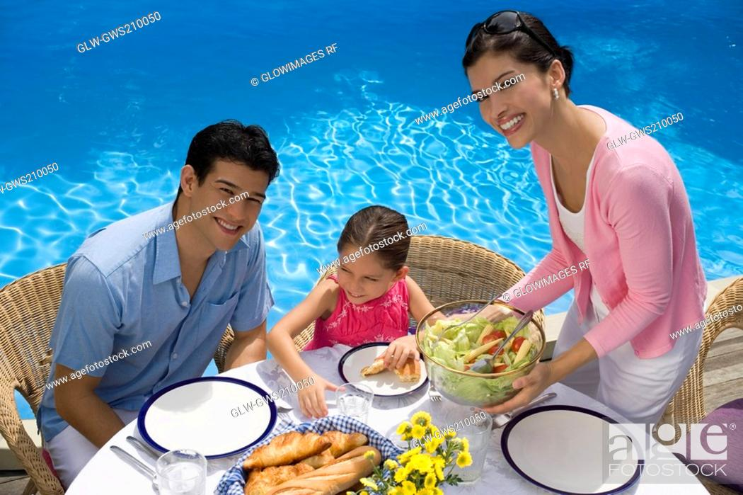 Stock Photo: Portrait of a young couple eating breakfast with their daughter.