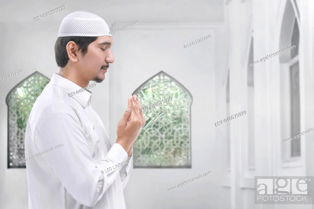 Stock Photo: Side view of asian muslim man praying inside the mosque.