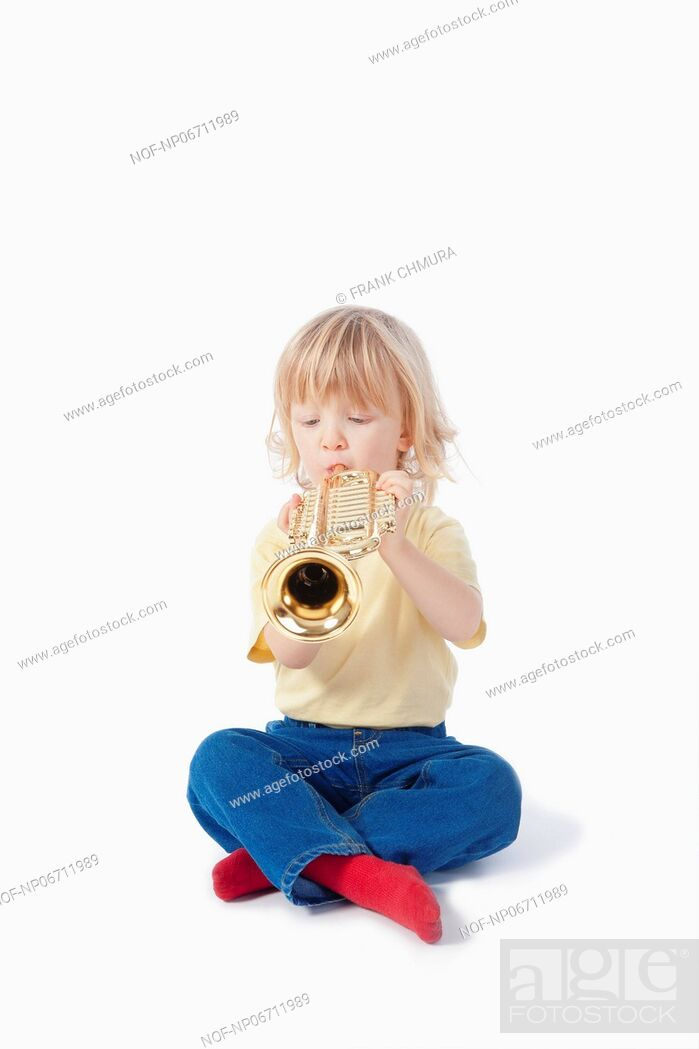 Stock Photo: boy with long blond hair playing with toy trumpet.