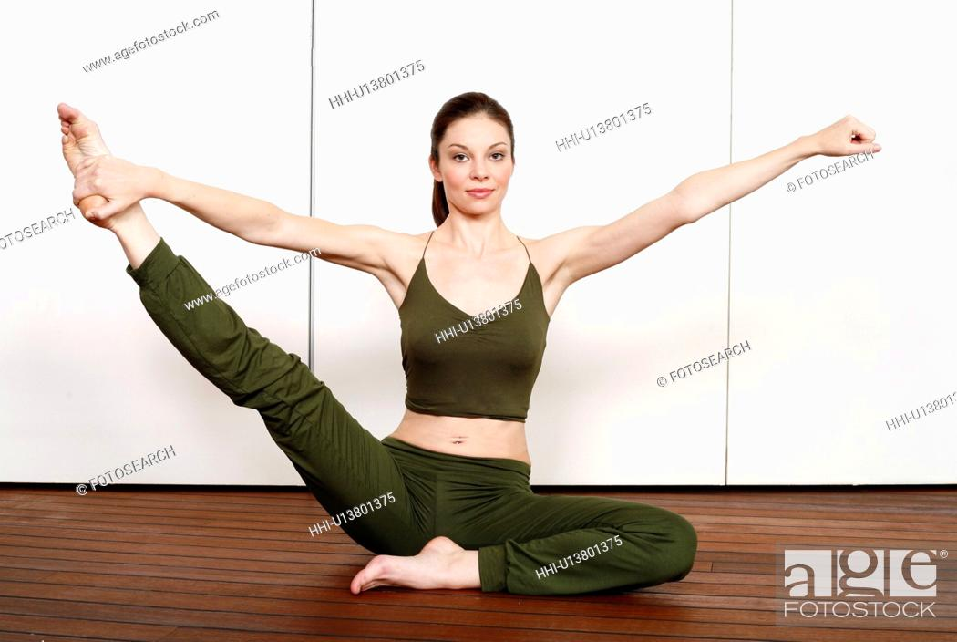 Stock Photo: Young woman performing a pilates stretch.