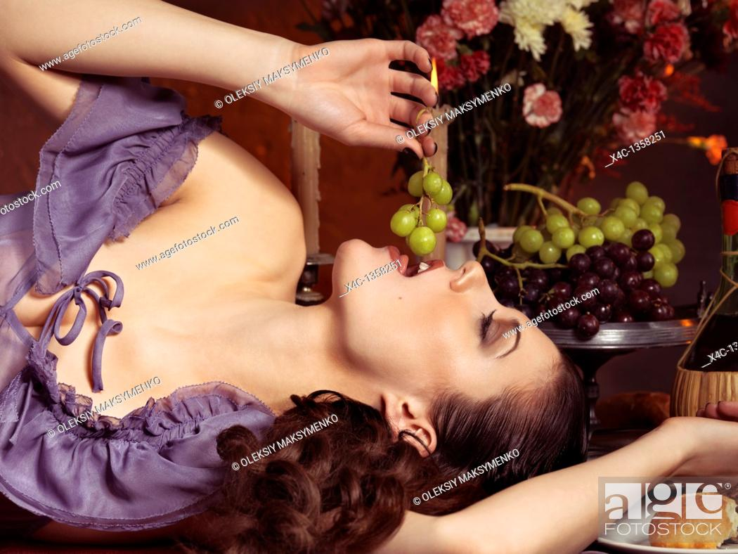 Stock Photo: High fashion photo of a beautiful woman lying on a festive table and eating grapes.