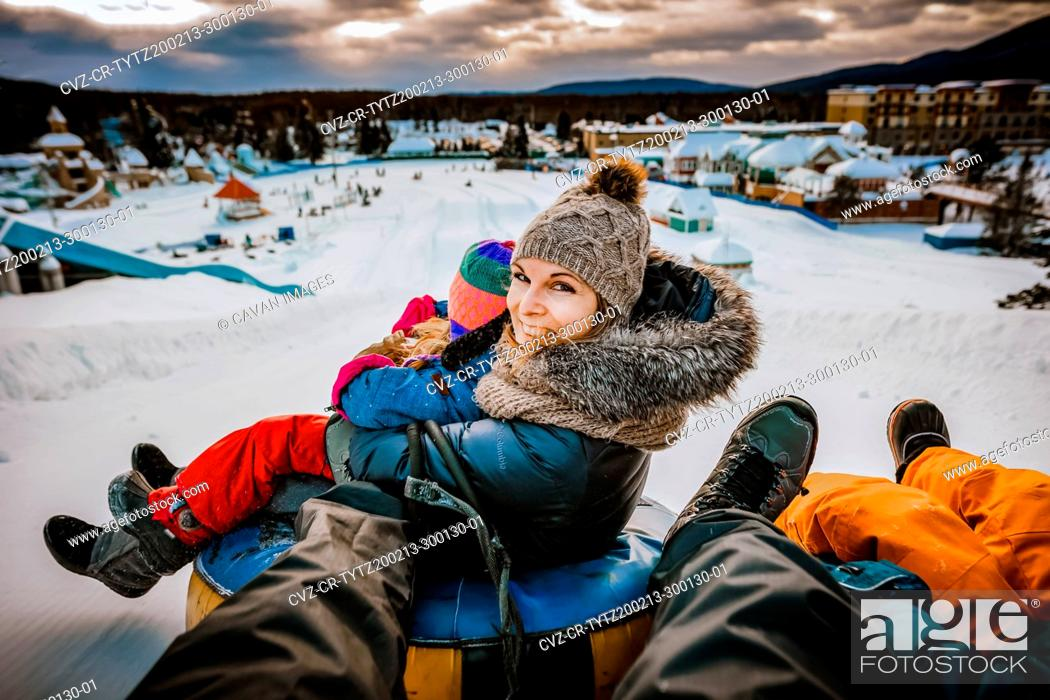 Stock Photo: Mother sliding with her family on tubes during a winter day.