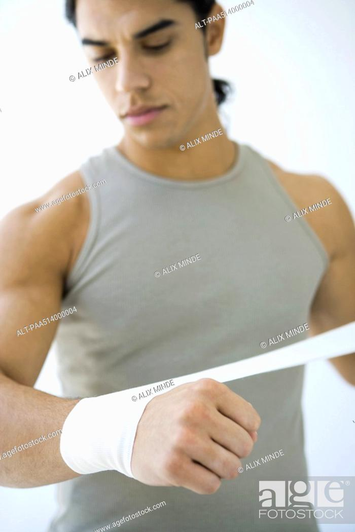Stock Photo: Man wrapping bandage around his wrist, looking down.