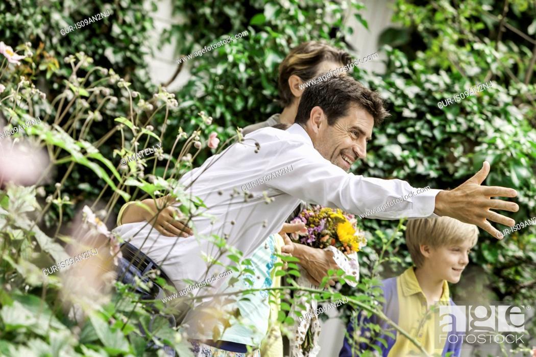 Imagen: Mature couple greeting grandchildren in garden.