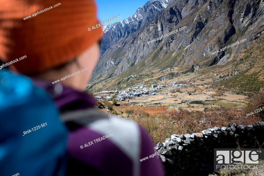 Stock Photo: A woman trekking in the Langtang valley rests near a chorten, Langtang Region, Himalayas, Nepal, Asia.