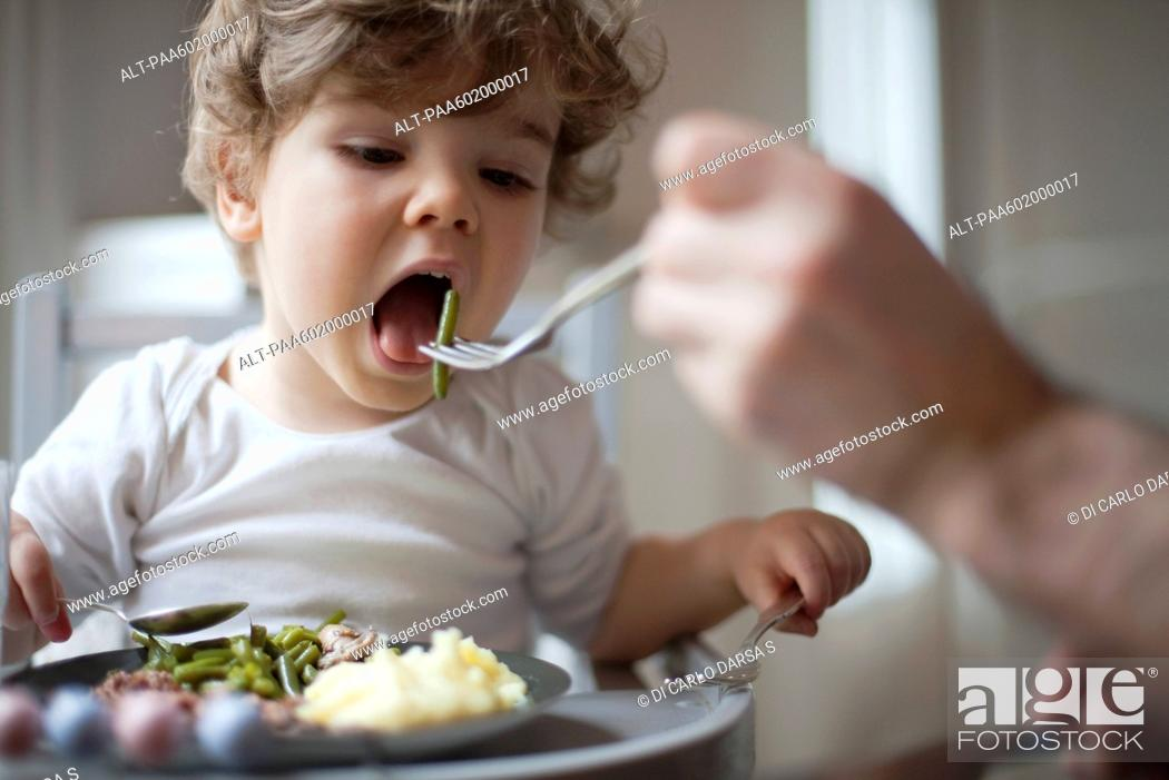 Stock Photo: Toddler boy being fed green beans, cropped.