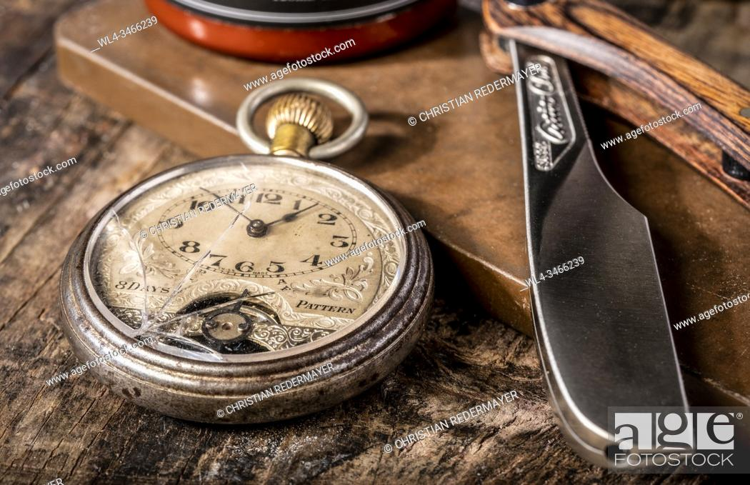 Stock Photo: Men's cosmetics shaving razor and a vintage pocket watch on a wooden background.