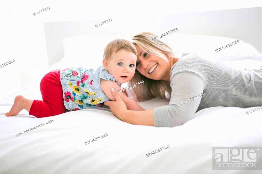 Stock Photo: A Pretty baby sit on mom in silk bed.