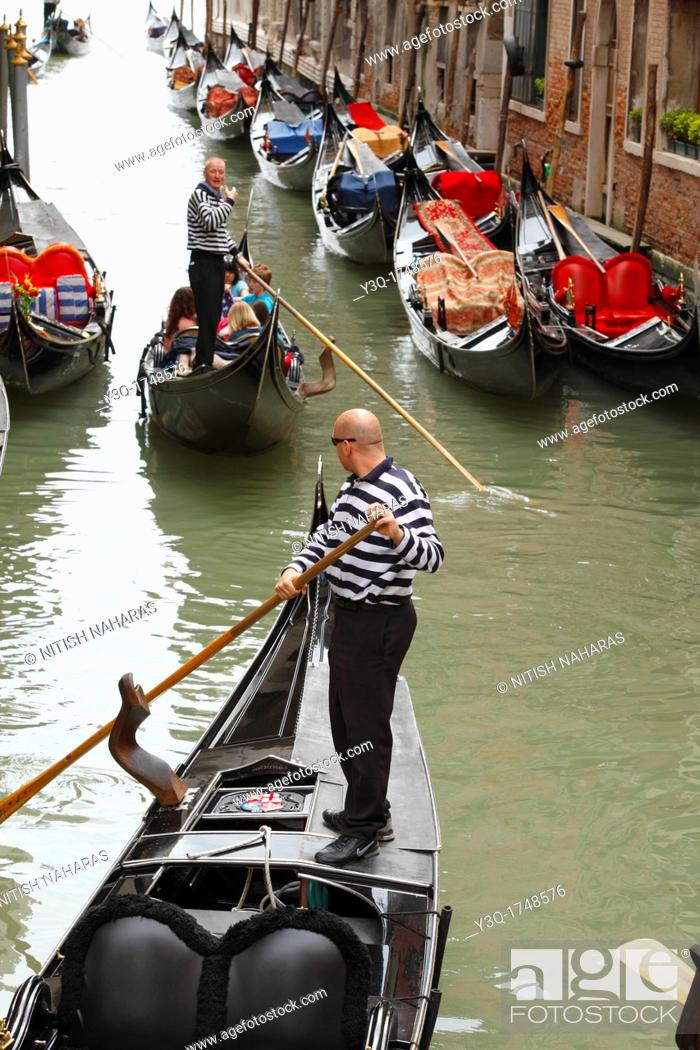 Stock Photo: Gondoliers negotiating canal traffic in Venice, Italy.