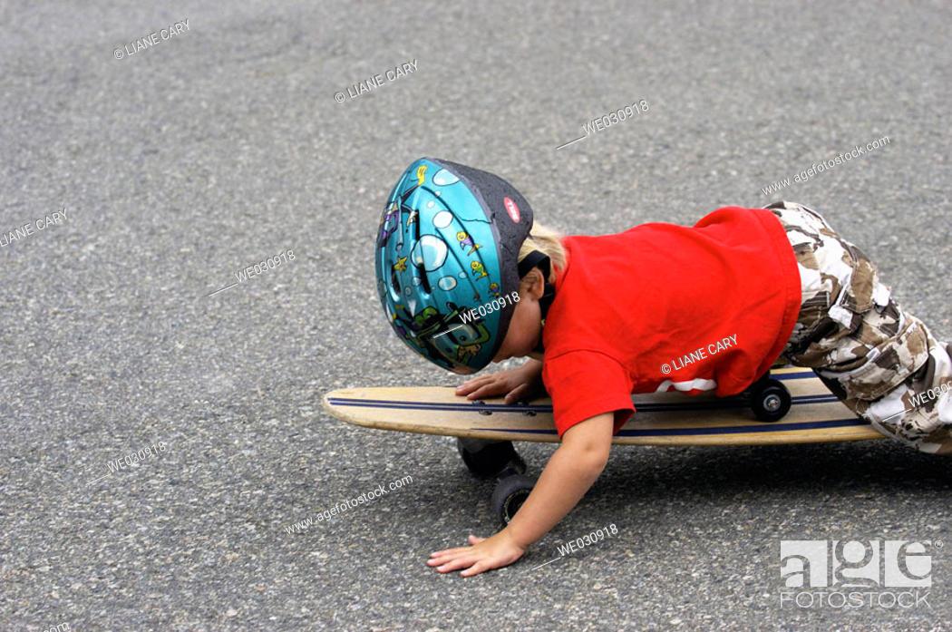Stock Photo: Boy lying on skateboard.