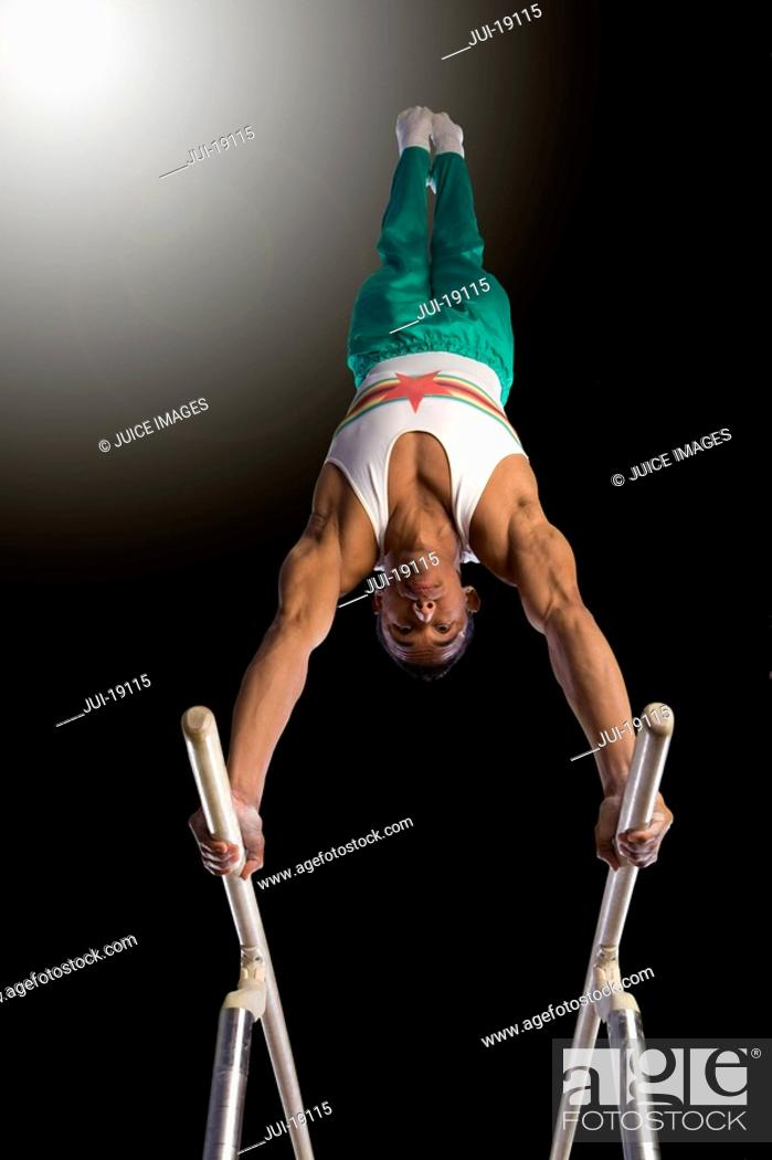 Stock Photo: Male gymnast performing handstand on parallel bars, low angle view.