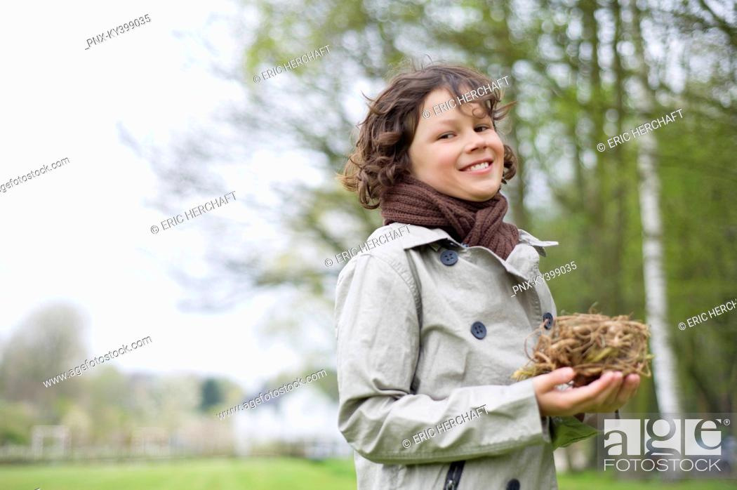 Stock Photo: Portrait of a boy holding a bird's nest in a park.