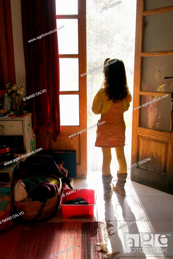 Stock Photo: Young girl standing by the door in her house, Ibiza, Spain.
