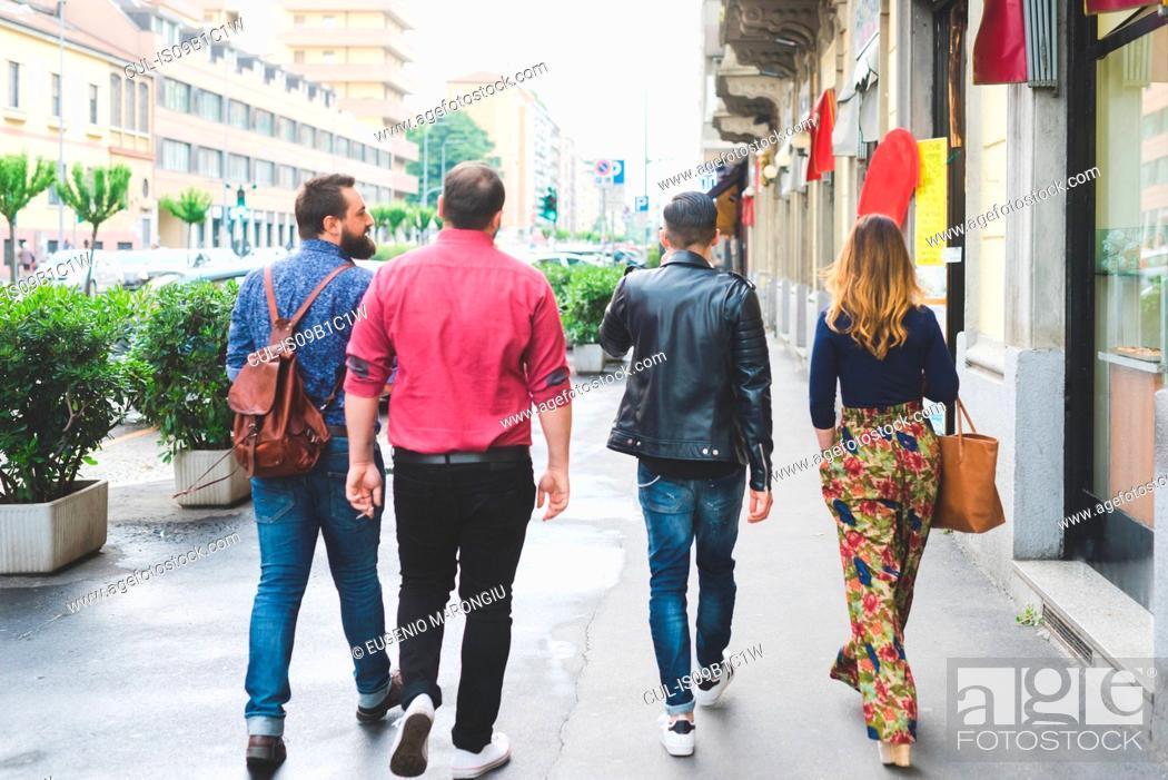 Stock Photo: Group of friends walking on sidewalk.