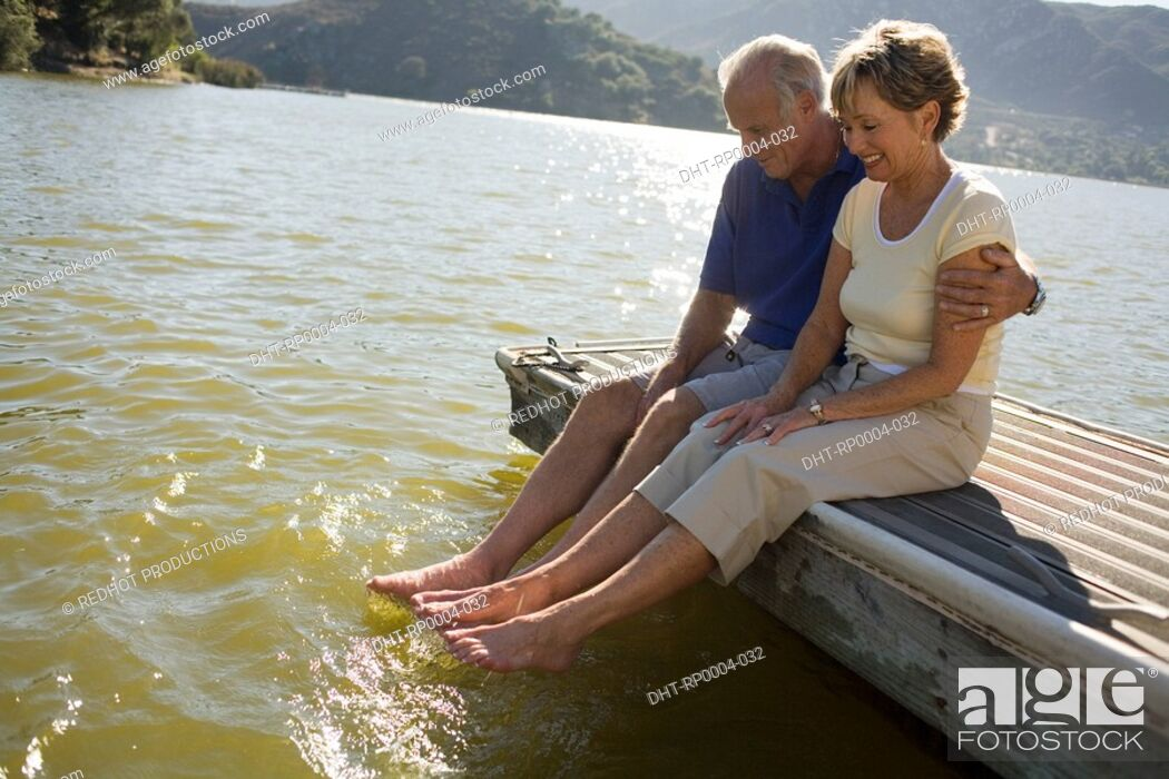 Stock Photo: A couple sitting on a dock.