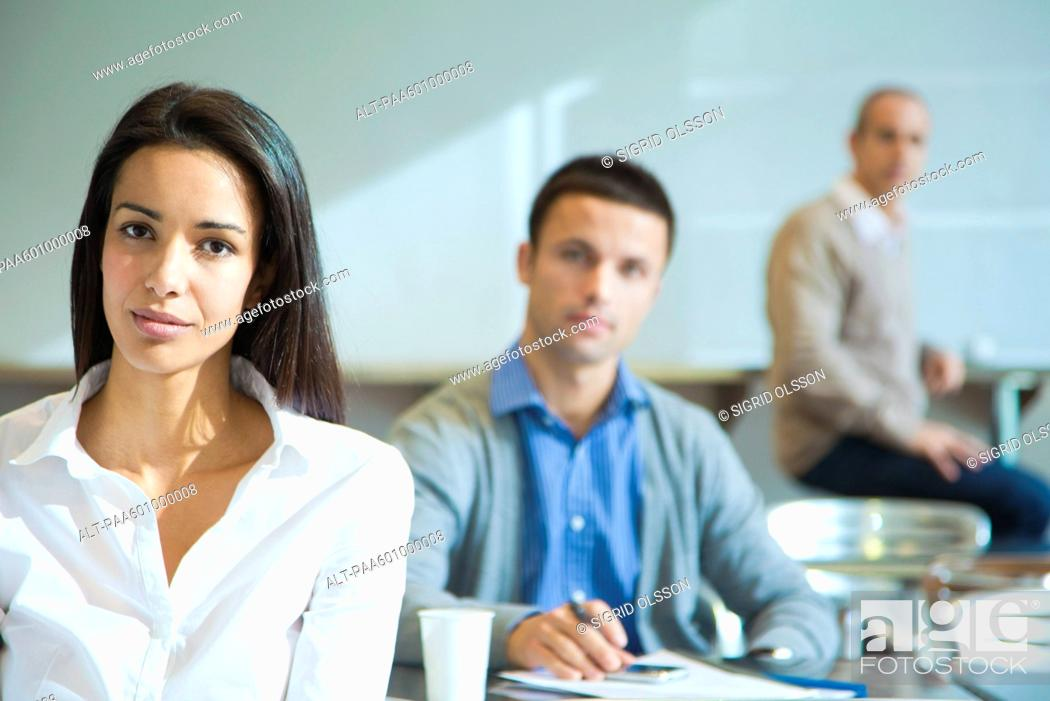 Stock Photo: Confident woman, men in background.