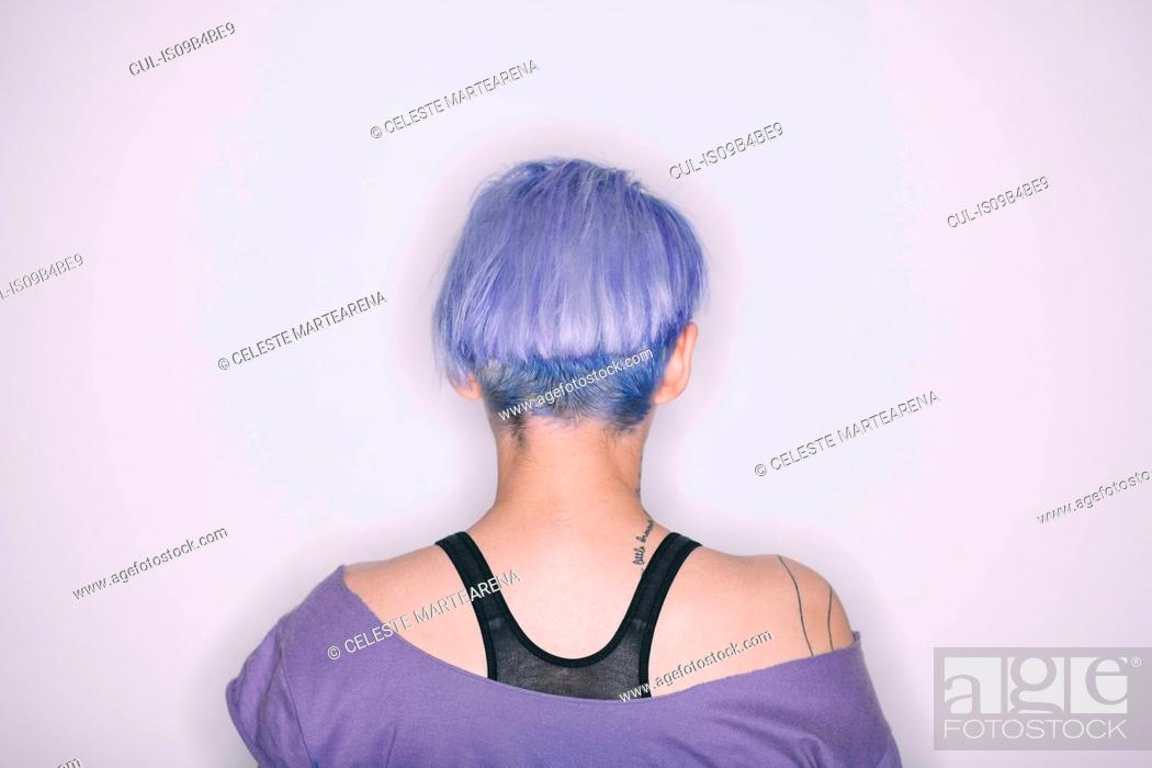 Stock Photo: Rear view of woman with purple hair and t-shirt.