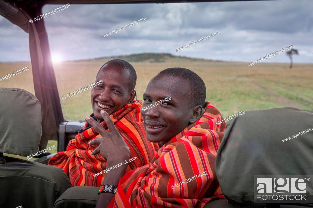 Stock Photo: Black men smiling in car in remote field.