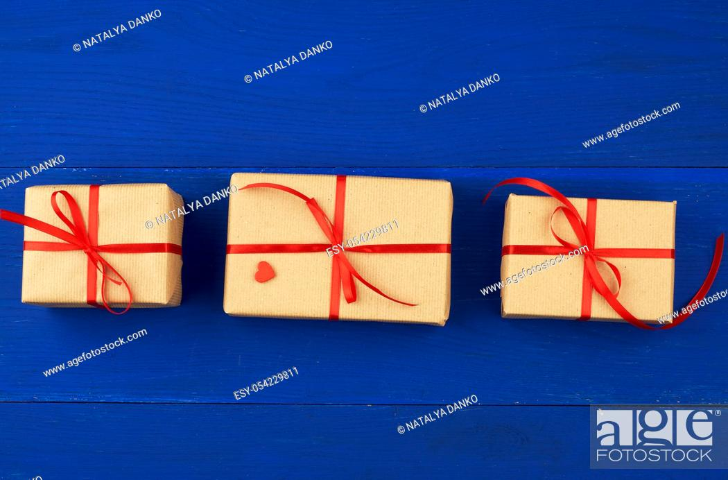 Stock Photo: gift wrapped in brown kraft paper and tied with a thin red ribbon on a blue wooden background, top view, flat lay. Eco package design.