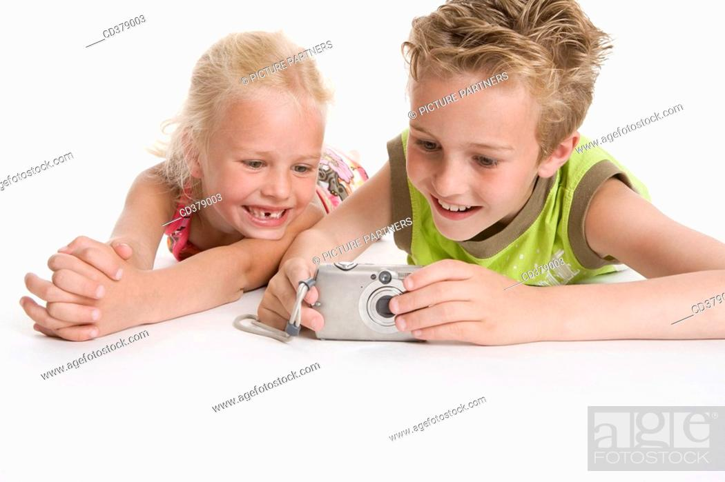 Stock Photo: Brother and sister looking at photos in the camera.