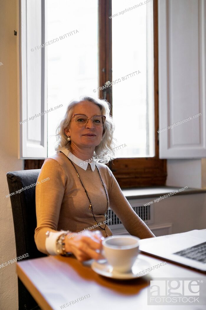 Stock Photo: Portrait of content mature businesswoman sitting at table with laptop and cup of coffee.