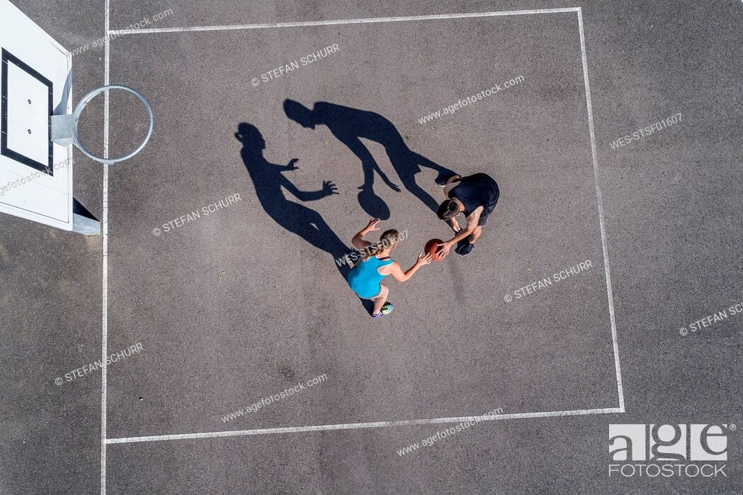 Stock Photo: Young man and woman playing basketball, aerial view.