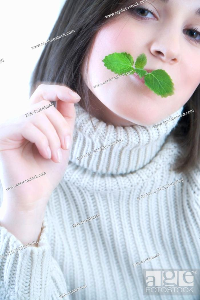 Stock Photo: woman with mint leaf in mouth.