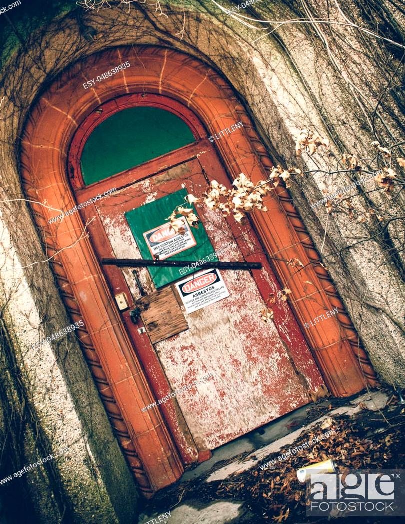 Stock Photo: View of exterior of abandoned psychiatric hospital with asbestos warning on door.