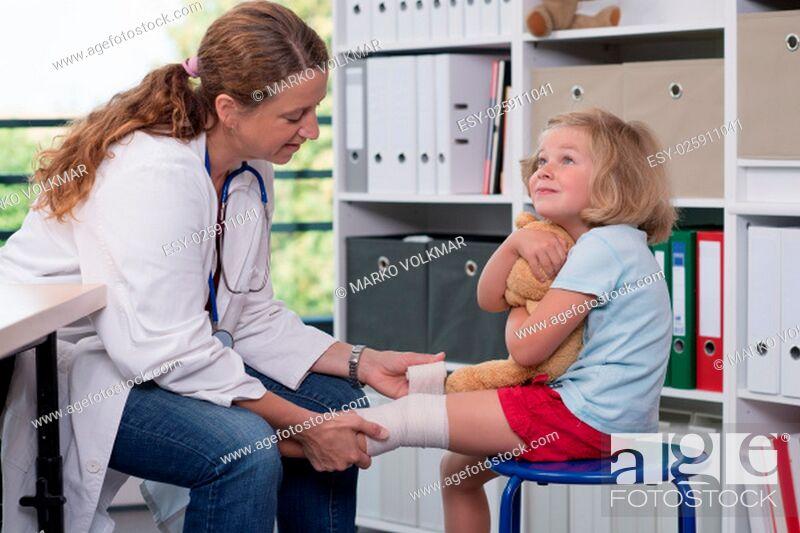 Stock Photo: female pediatrician in white lab coat bandaging the leg of a little girl.