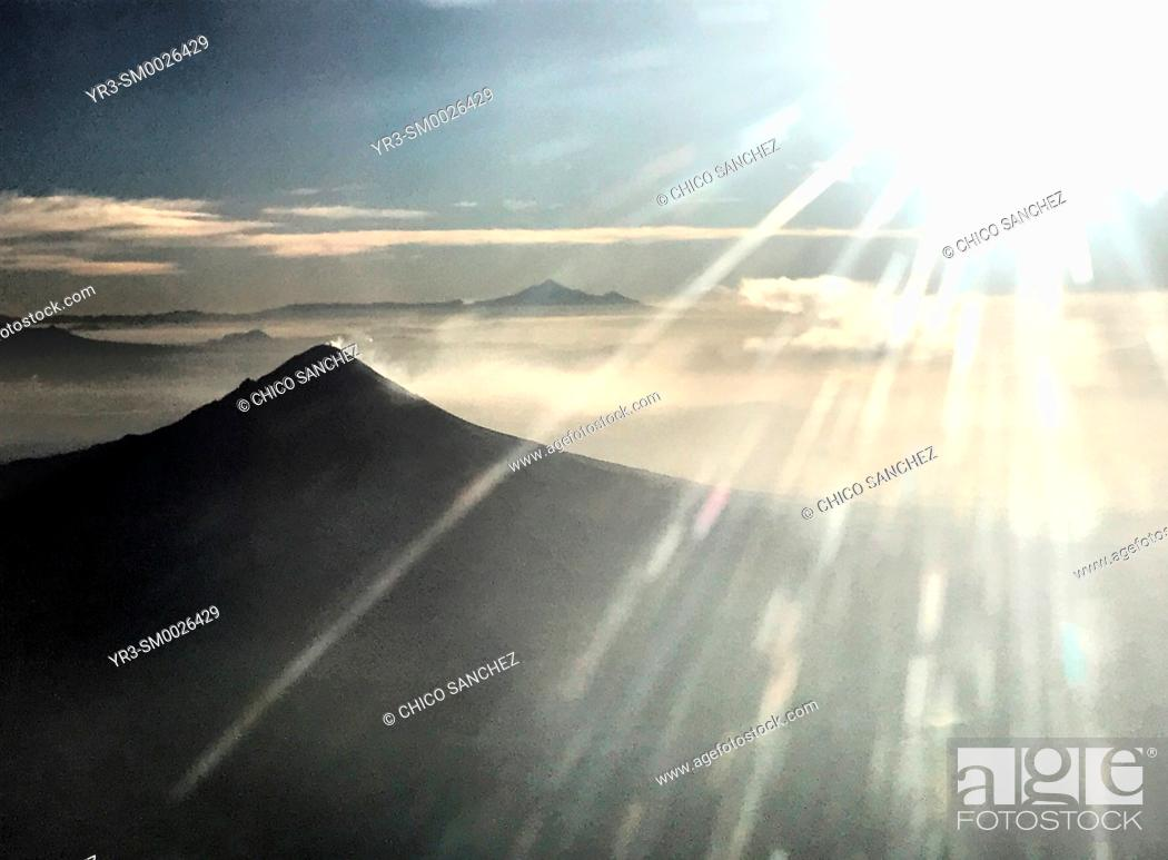 Stock Photo: The sun shines in the window of a plane over the Popocatepetl volcano in Puebla, Mexico.