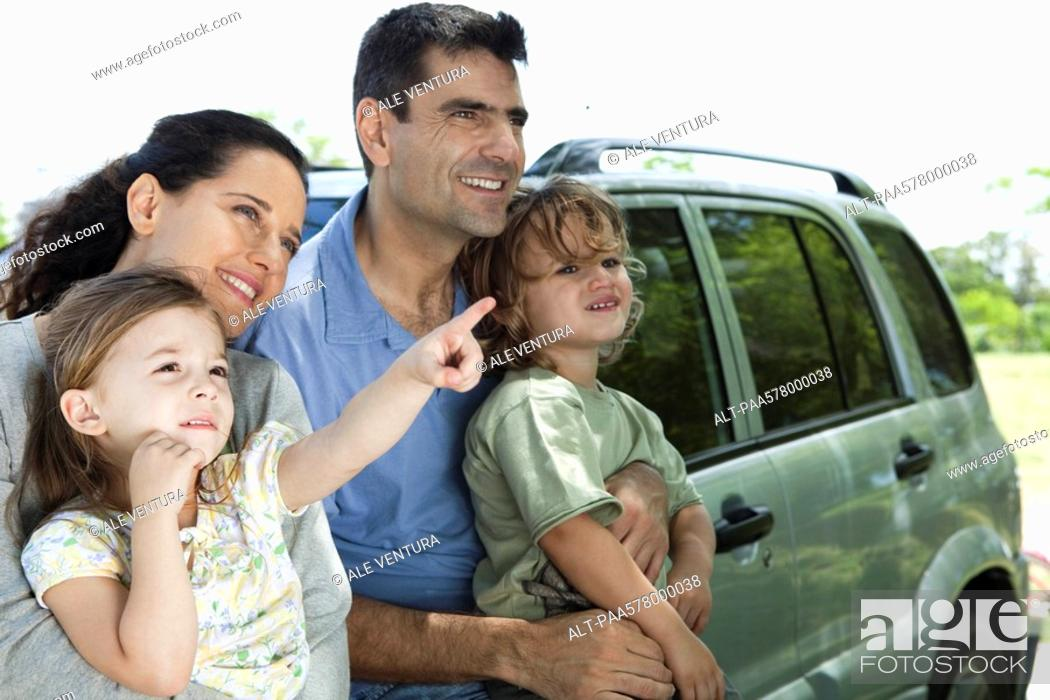 Stock Photo: Family leaning against car, all looking as daughter points at something in distance.
