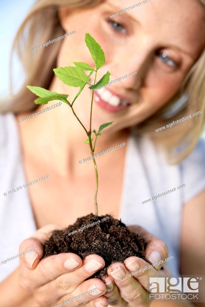 Stock Photo: Germany, Cologne, Young woman holding seedling, smiling.