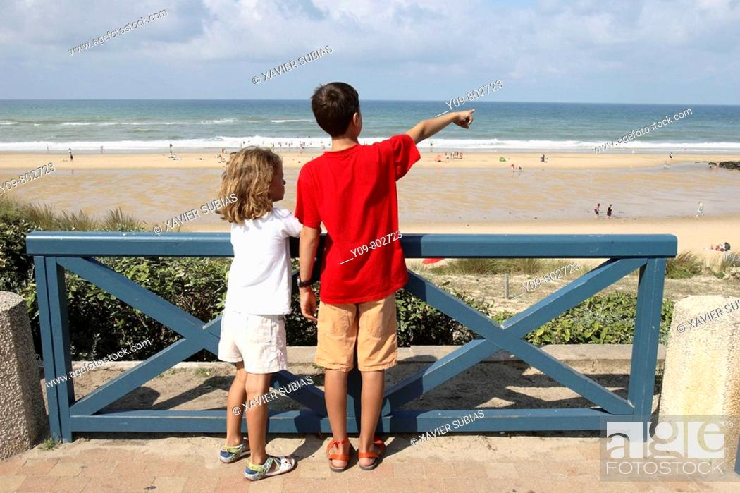 Stock Photo: Boy and girl looking at the sea, Lacanau-Océan. Gironde, Aquitaine, France.