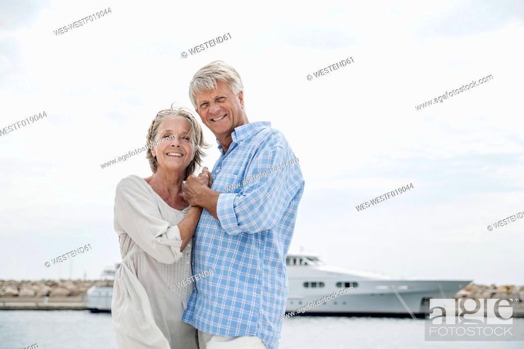 Stock Photo: Spain, Senior couple at harbour, smiling, portrait.