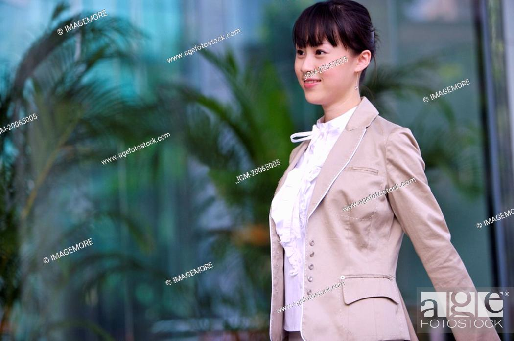 Stock Photo: Young woman walking and smiling.