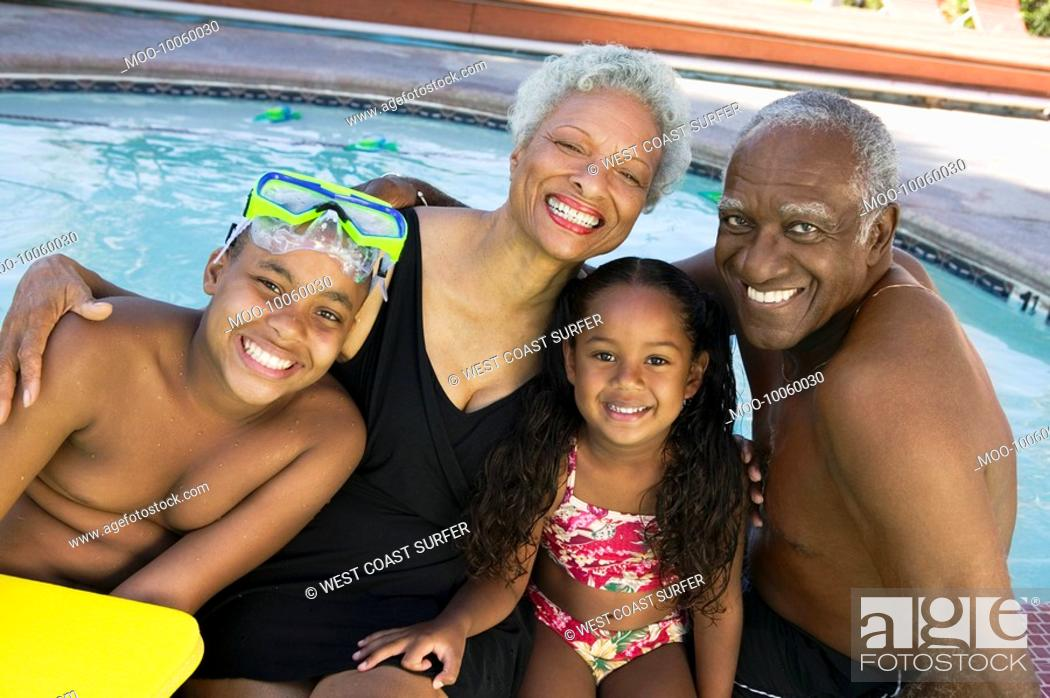 Stock Photo: Girl 5-6 boy 10-12 with grandparents at swimming pool portrait.