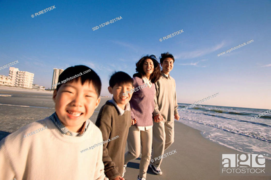 Stock Photo: Parents and their two sons holding hands walking on the beach.