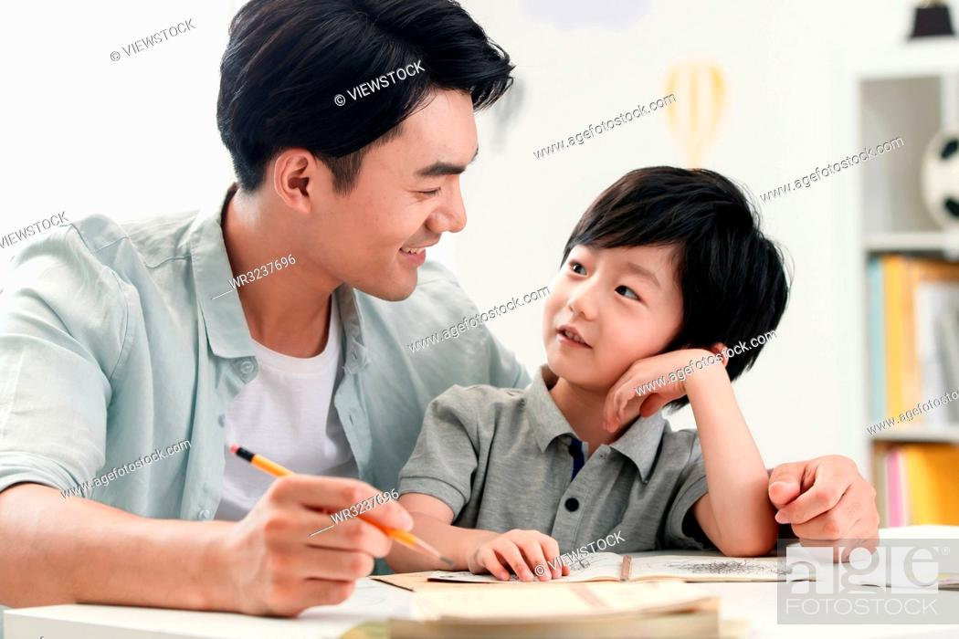 Stock Photo: Dad counselling son do his homework.