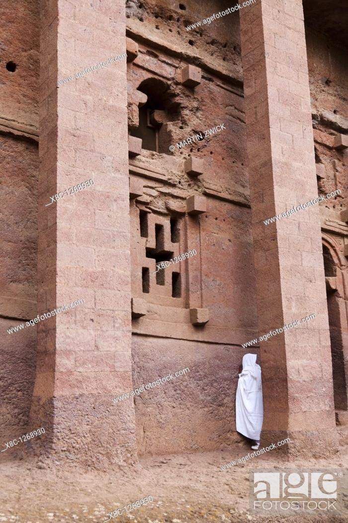 Stock Photo: The rock-hewn churches of Lalibela in Ethiopia  Pilgrim praying in front of a church  The churches of Lalibela have been constructed in the 12th or 13th century.