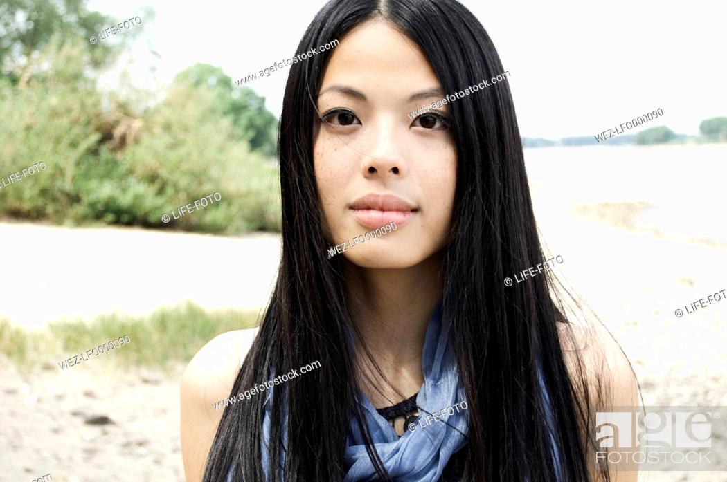Stock Photo: Germany, Close up of young woman at Rhine riverside, portrait, smiling.