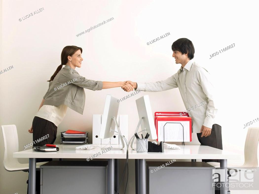 Stock Photo: Man and Woman Shaking Hands over Desks side view.