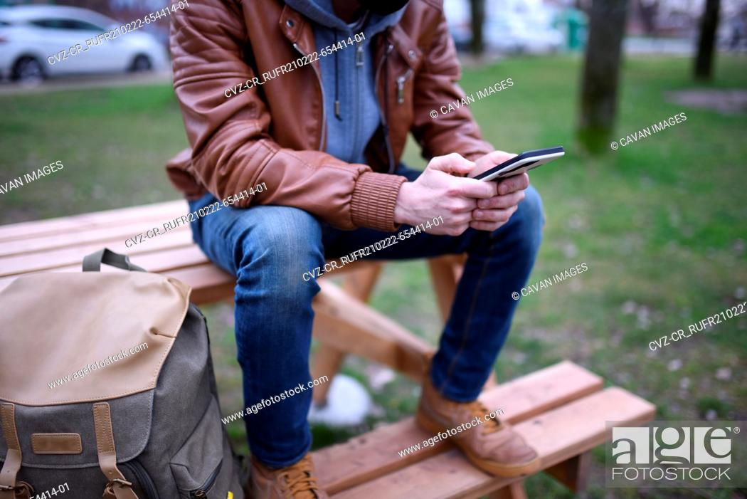 Stock Photo: Image focused on the hands of a man with his mobile phone on a wooden bench in an open space.