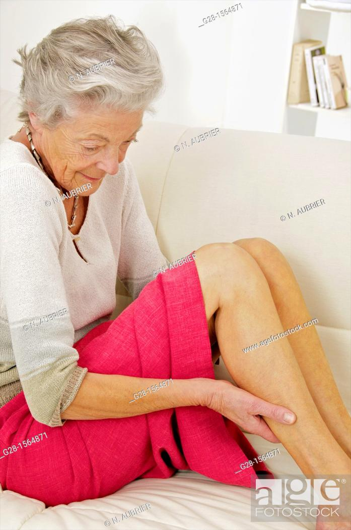 Stock Photo: Senior woman holding her painful thigh on her sofa.