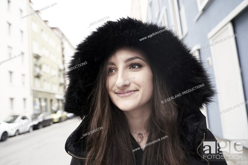 Stock Photo: Young woman in hooded jacket. Munich, Germany.