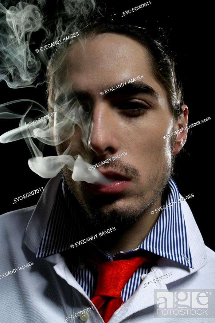 Stock Photo: Close-up of young man with smoke coming out of his mouth.
