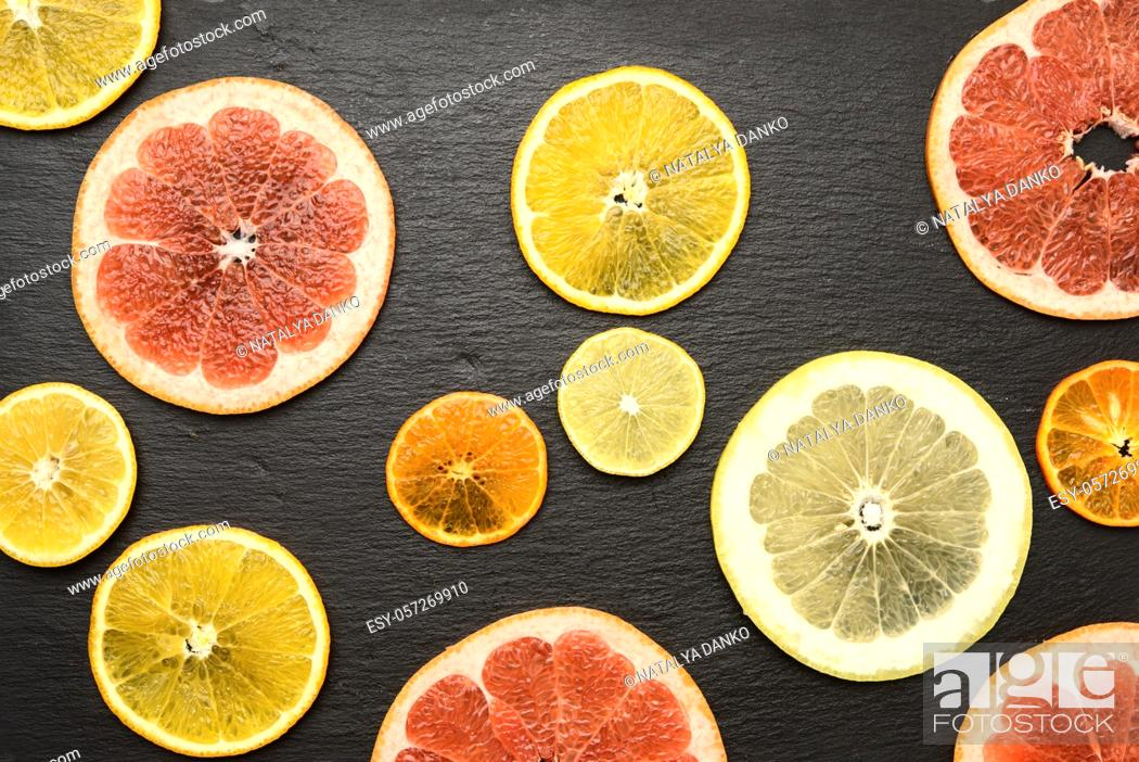 Stock Photo: citrus fruits cut into round pieces: orange, grapefruit, lemon, tangerine. Ripe and juicy fruits on black background.