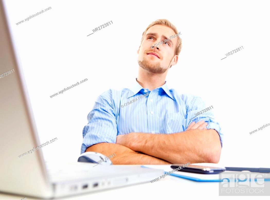 Photo de stock: young man at desk in office thinking, contemplating.