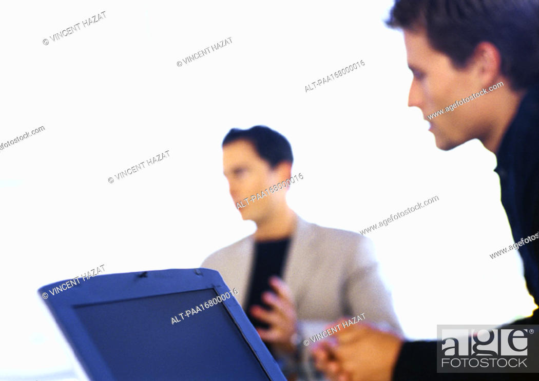 Stock Photo: Two men, one with laptop computer, blurred.