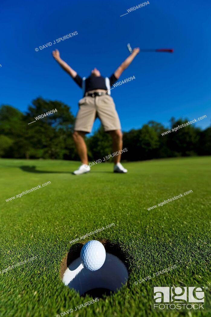 Stock Photo: A Golfer celebrates a successful put.