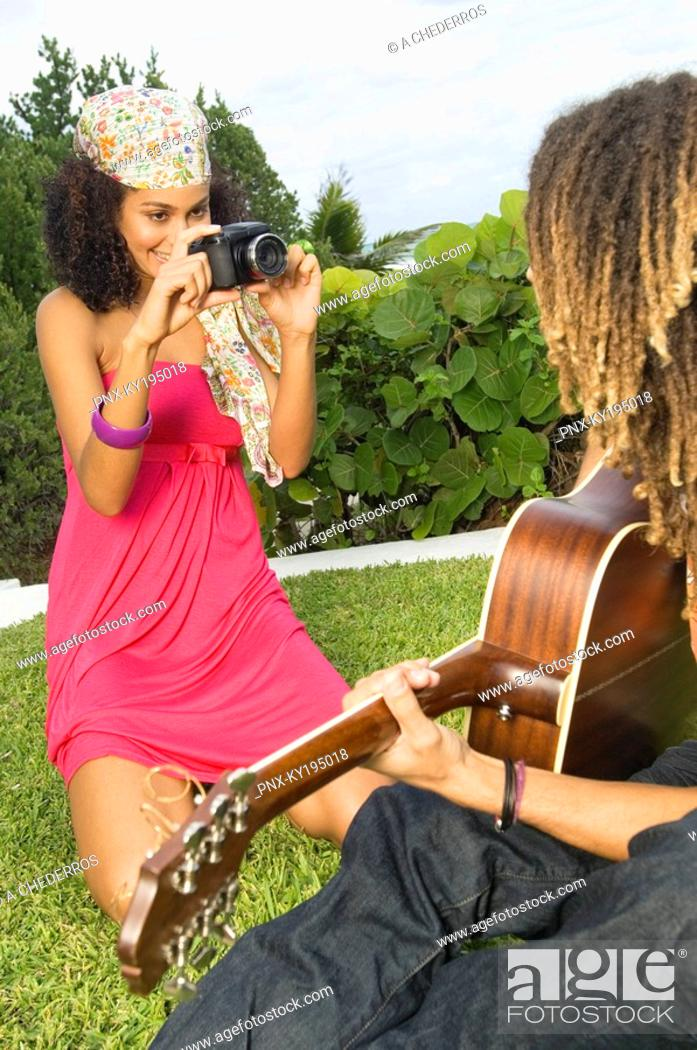 Stock Photo: Woman taking a picture of a man playing a guitar.